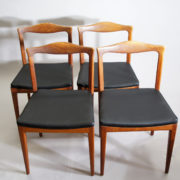 Four side chairs in teak with seat cover in leather imitation.